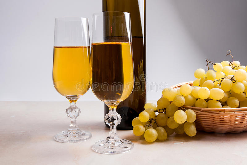 White wine and grapes. White wine in glasses, bottle of wine and. Two glasses with white wine and brown bottle of white wine on light marble background. Bunch of royalty free stock images