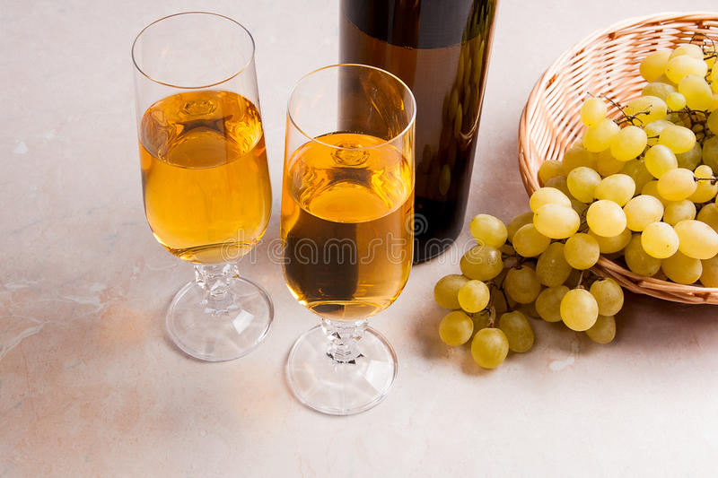 White wine and grapes. White wine in glasses, bottle of wine and. Two glasses with white wine and brown bottle of white wine on light marble background. Bunch of royalty free stock photography