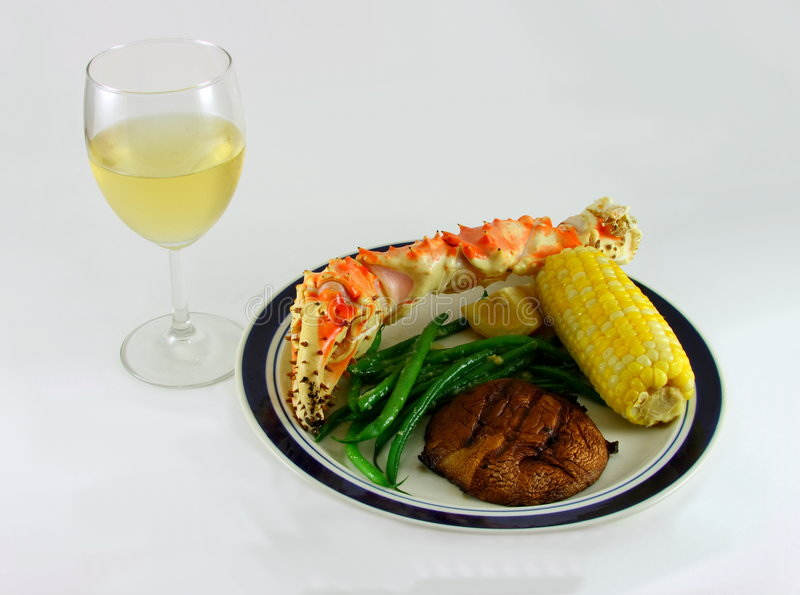 White Wine and King Crab Leg. White wine, king crab leg, corn on the cob, green beans and potato royalty free stock images