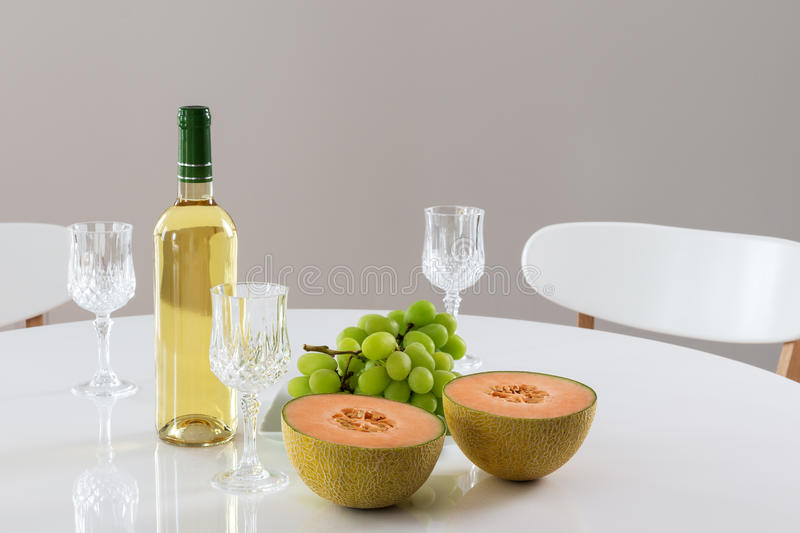 White wine, melon and grapes. Round table with white wine, melon and green grapes royalty free stock images