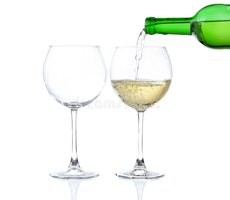 White wine poured into glass. On white royalty free stock images
