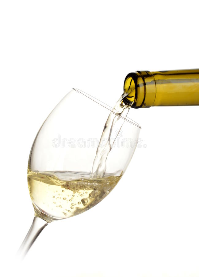 White wine poured into a glass. On white background royalty free stock images