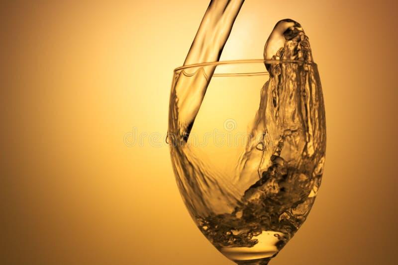 White wine pouring. On white background stock photos