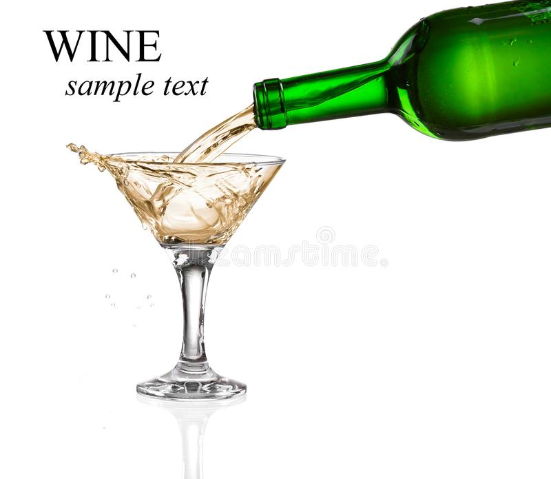 White wine pouring from the bottle intro the glass royalty free stock image