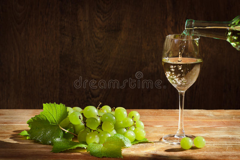 White wine pouring down to the glass with grapes royalty free stock photo