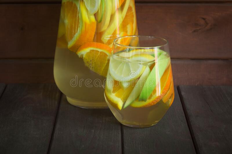White wine sangria with orange, lemon and green apple in glass and pitcher. stock photos