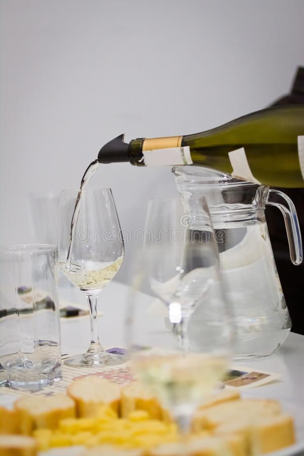 White wine sauvignon blanc pour into wineglass during wine testing in a wine shop royalty free stock photos