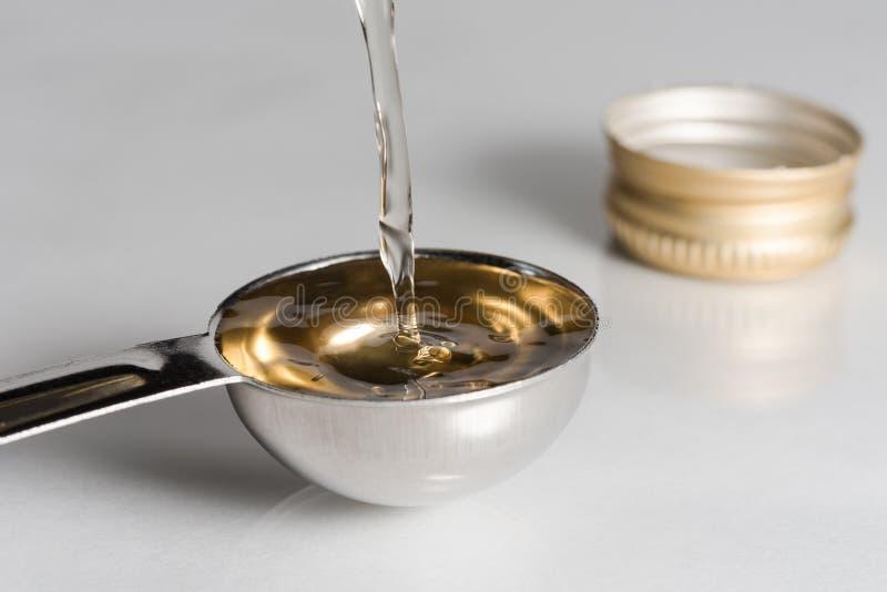 Pouring White Wine Vinegar into a Teaspoon stock photos