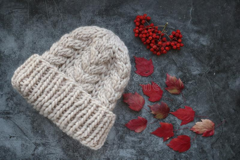 White winter handmade knitted hat with rowan berries and red autumn maple leaves on grey marble background, horizontal stock photos