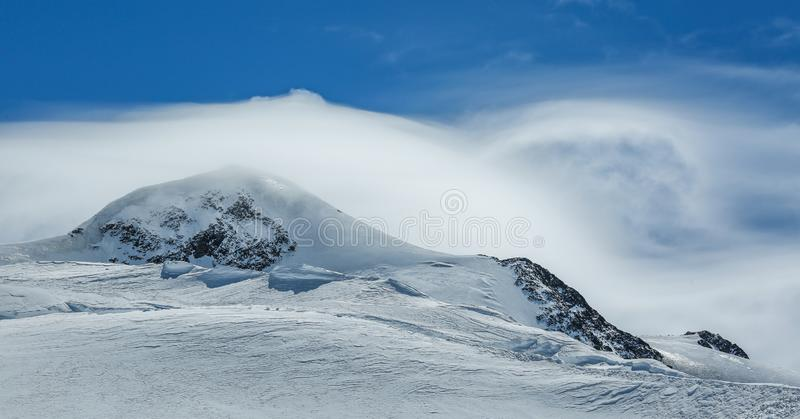 White winter mountains covered with snow in blue cloudy sky. Alps. Austria. Pitztaler Gletscher. Wildspitzbahn. Winter season royalty free stock photos