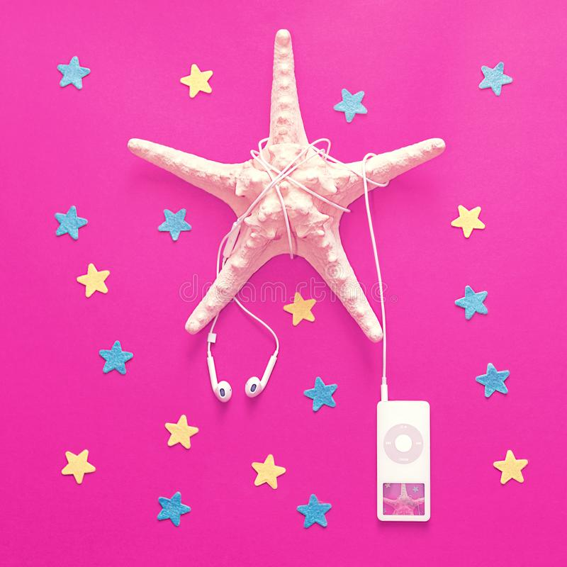 White wired headphones are connected to a music player. The wire is wound on a large starfish. royalty free stock photo