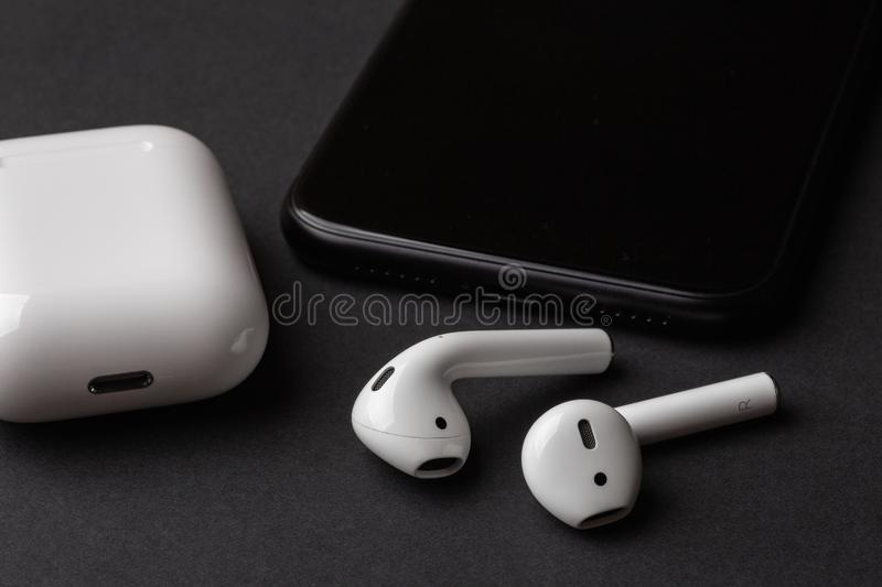 White wireless bluetooth earphones or headphones, plastic case or box for storage and charging and smartphone on black background royalty free stock photo