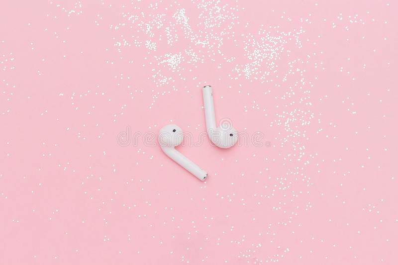 White wireless Bluetooth headphones and glitter confetti on pink paper background. Template for text or your design. Flat lay Top stock photos