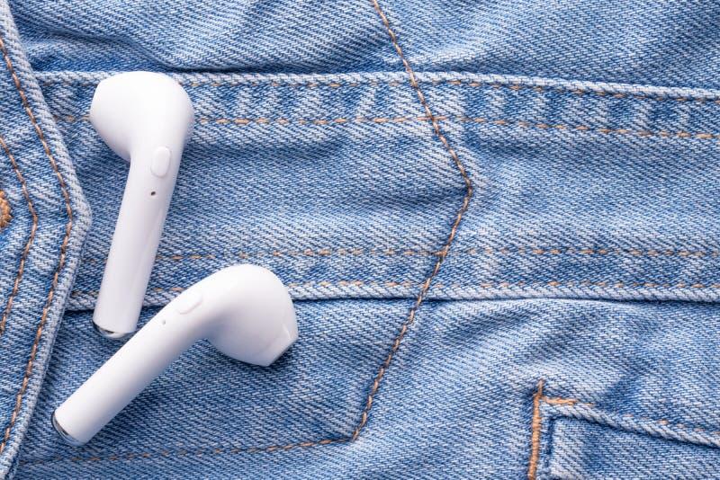 White wireless headphones in jeans pocket stock photo