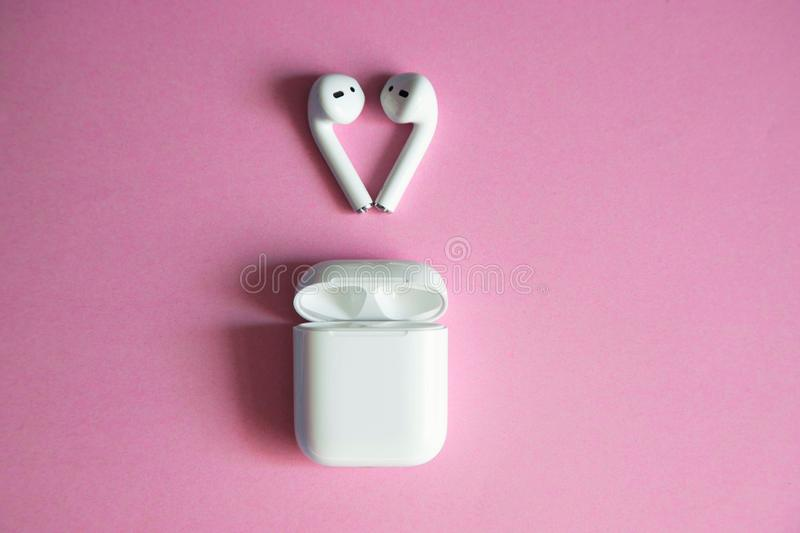 White wireless headphones lying over an open charger on a pink background. Place for text. stock photos
