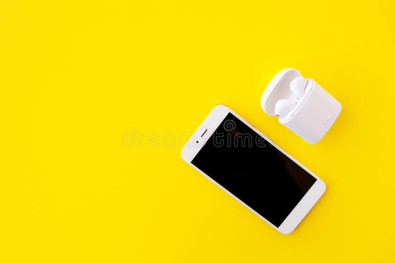 White wireless headphones and smartphone are lying on a bright yellow background. Headphones in charging case. stock image