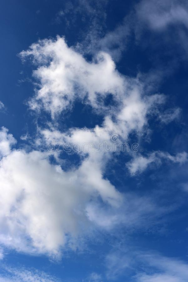 White wispy cloud against a blue sky stock image
