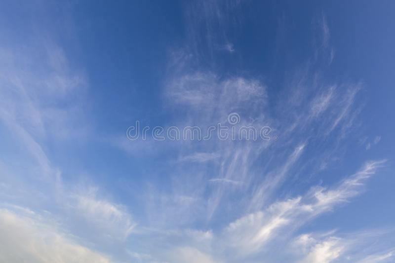 White wispy clouds and blue sky 0537. Wispy white clouds in a clear blue sky background. Cloudscape viewpoint stock image