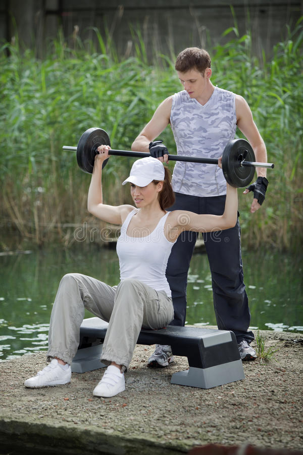 Woman Exercising With Personal Trainer With Barbell - Outdoor Stock Photos