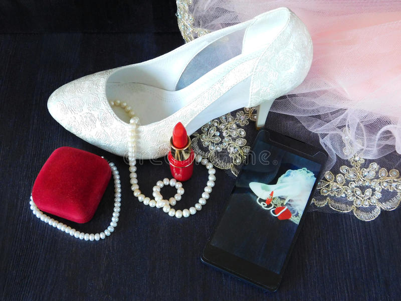 White women`s shoes with high heels, red lipstick, present box and smartphone with the photo in the screen. White women`s shoes with high heels, red lipstick and royalty free stock photos