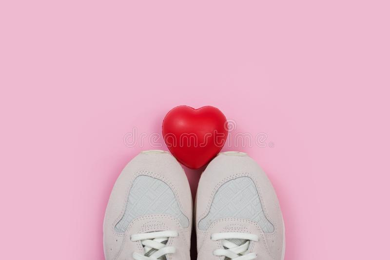 Women`s sneakers on the red background with heart symbol for the Valentine`s Day or Shoe Sale. White women`s sneakers on the red background with heart symbol for royalty free stock photo