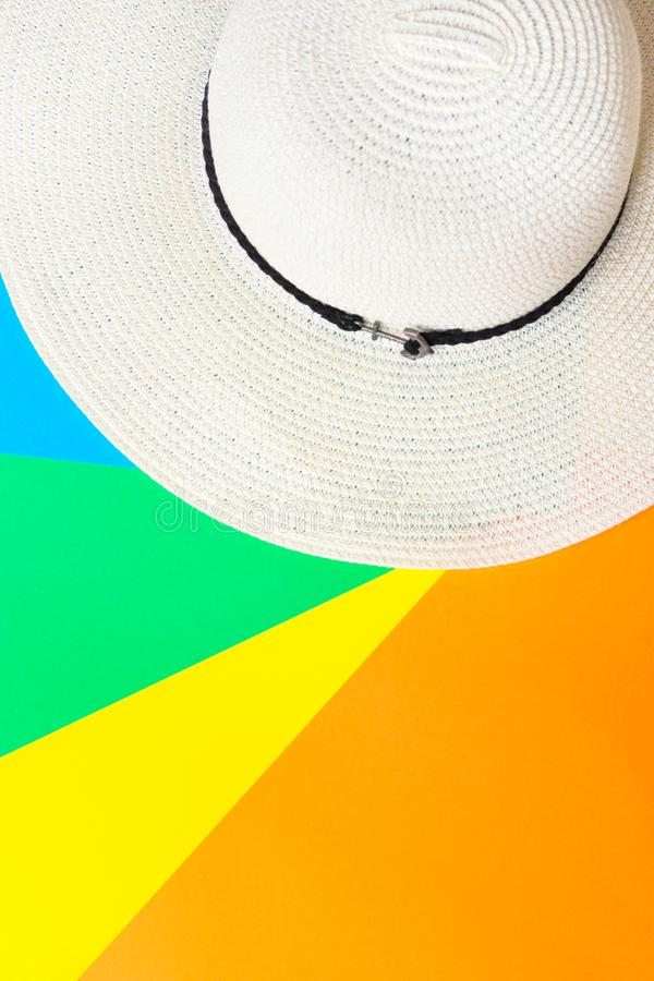 White women`s straw beach hat on rainbow multicolored pinwheel striped sunburst background. Summer vacation fashion stock images