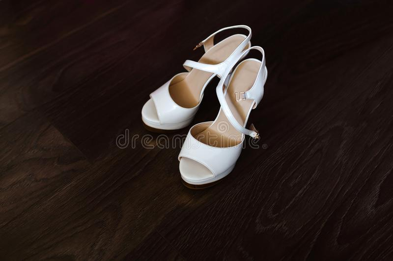 White women`s wedding shoes. With buckles stand on a wooden floor with a beautiful texture stock photography