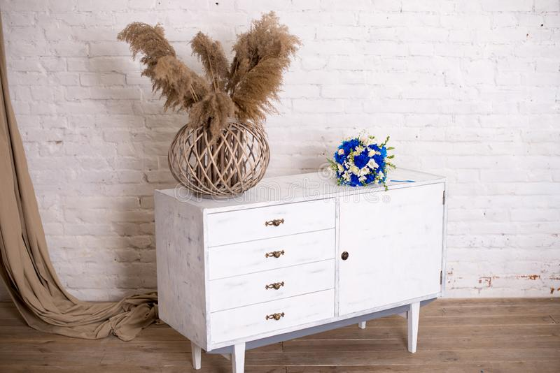 White wood bedside table, dresser in bedroom. bridal bouquet on the nightstand vase with flowers. interior. Series of. Furniture loft style. Modern designer stock photos