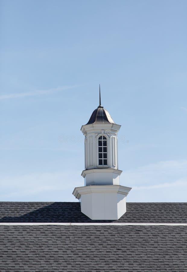White Wood Cupola on Asphalt Shingles. A white wood cuploa under blue skies on an asphalt shingle roof stock image