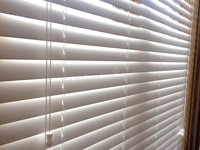 White Wood window blinds. White faux wood horizontal window blinds with slats and cord controls, window covering treatments for privacy, light control and royalty free stock photo