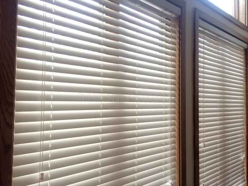 2 White Wood window blinds. White faux wood horizontal window blinds with slats and cord controls, window covering treatments for privacy, light control and stock image