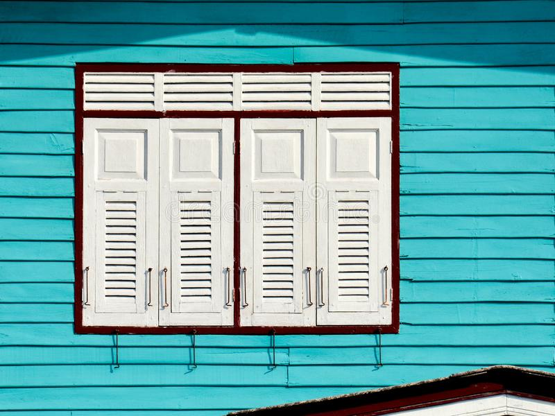 White wood window at blue house. stock photo
