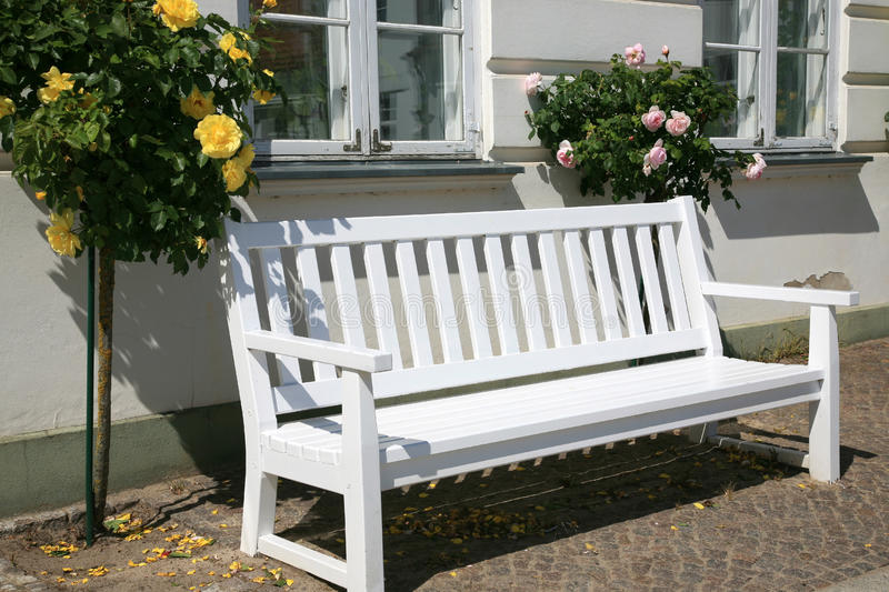 Wit Bankje Voor Buiten.A Wooden Bench In The Garden Surrounded By Bushes Stock Image