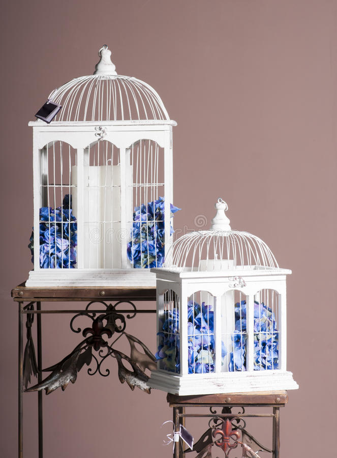White wooden bird cages with blue hydrangeas royalty free stock photos