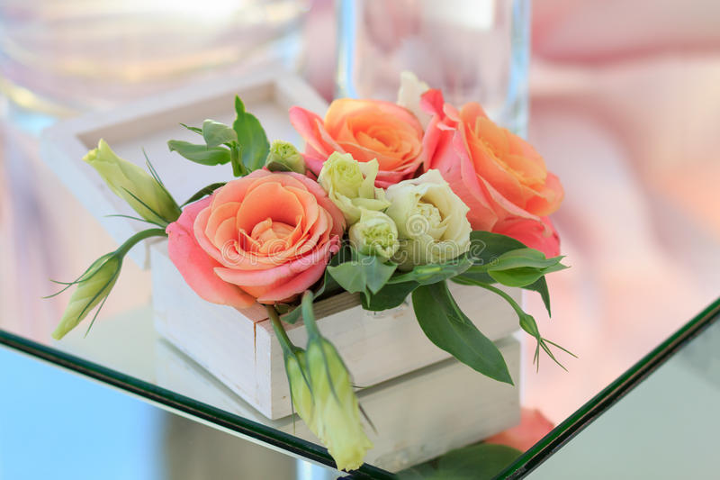 White wooden box with fresh flowers stands on a mirrored table stock image