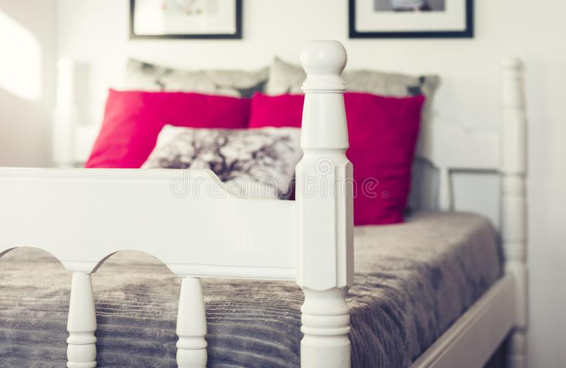 White wooden carved bed with gray bedspread and red pillows royalty free stock photography