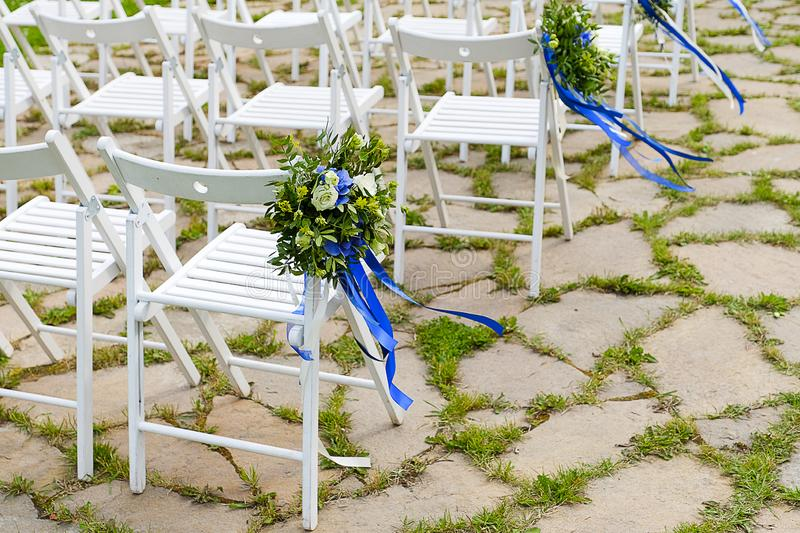 White wooden chairs decorated with bouquets of flowers and bright satin ribbons, outdoors. Wedding decor at the ceremony.  royalty free stock images