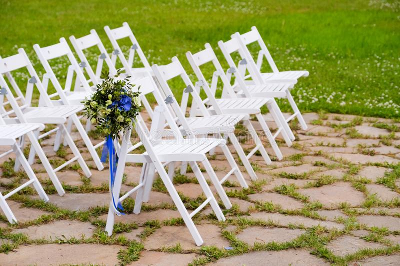 White wooden chairs decorated with flowers and bright satin ribbons, wedding decor at the ceremony.  stock photos