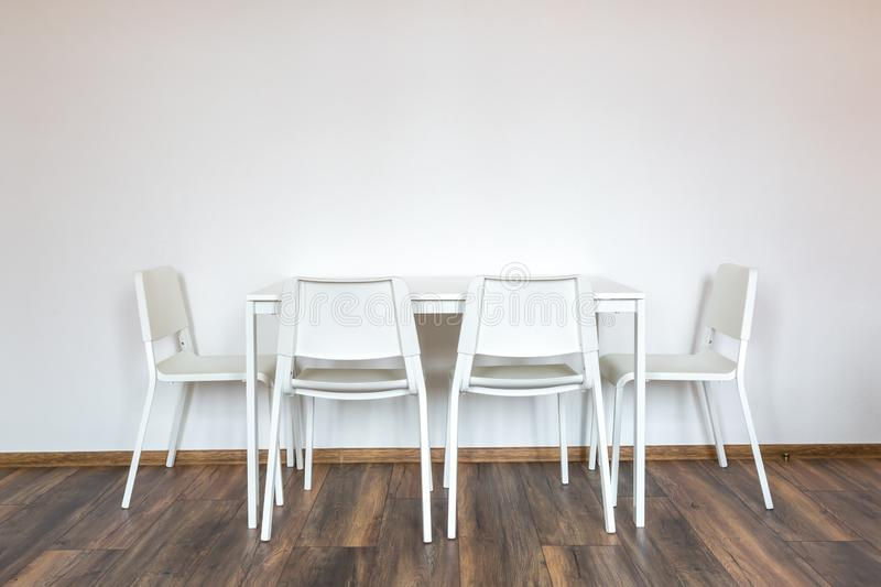 White wooden chairs with a table against the background of a white wall in the interior stock images