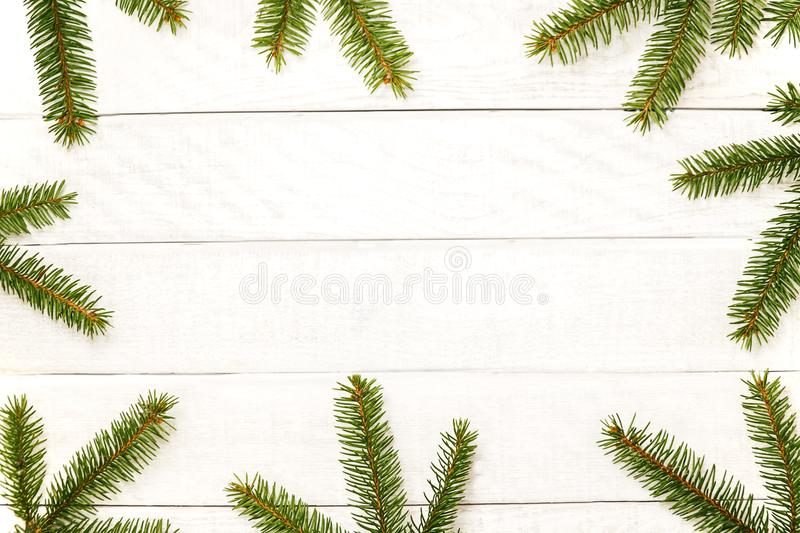White wooden Christmas background. Border decorated fir branches. Copy space for holiday greetings. lovely xmas festive card. Top view. Flat Happy New Year royalty free stock photo
