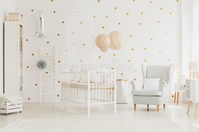 Wooden crib with canopy. White wooden crib with canopy in bright baby room with silver balloon, grey armchair and dotted wall stock photos