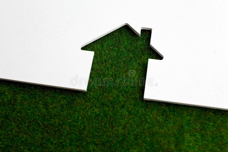 White wooden cut of house on fresh green grass. Wooden cut of house on fresh green grass stock photos