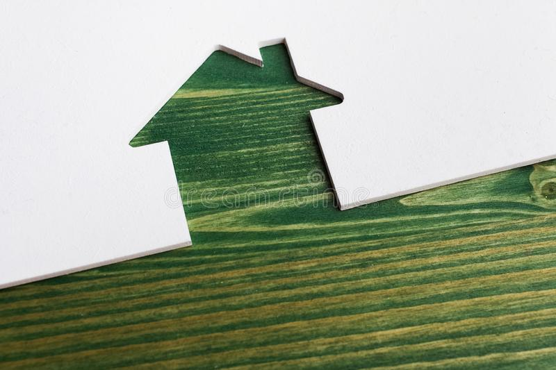 White wooden cut of house on green background. Wooden cut of house on green wooden background stock photography