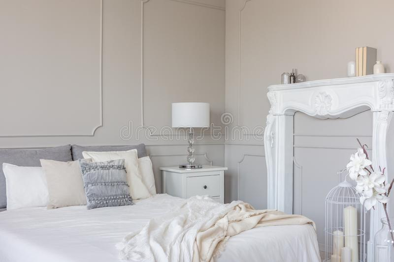 White wooden fireplace portal in beautiful bedroom interior with white sheets on king size bed. White wooden fireplace portal in beautiful bedroom interior with stock images