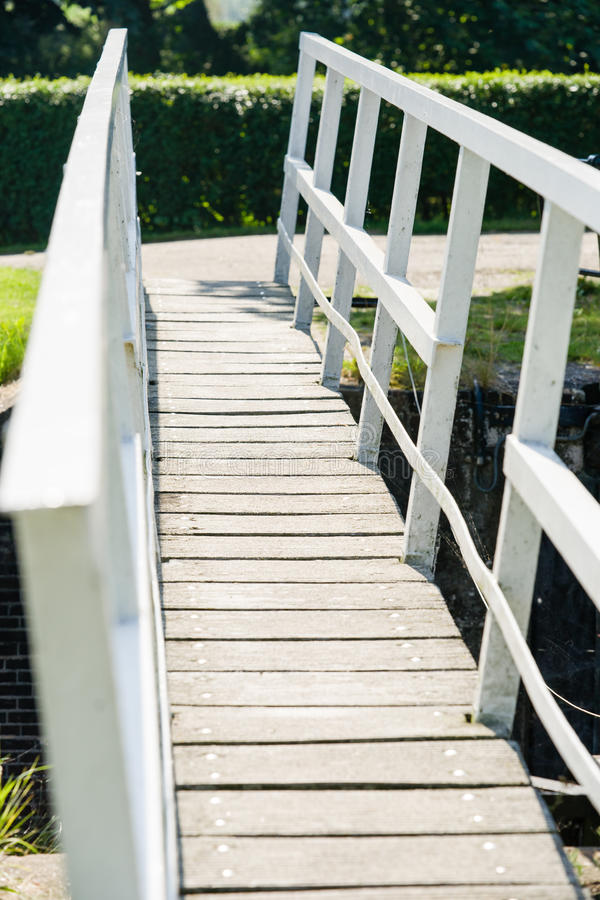 White wooden foot bridge over a narrow river on a sunny day royalty free stock photos
