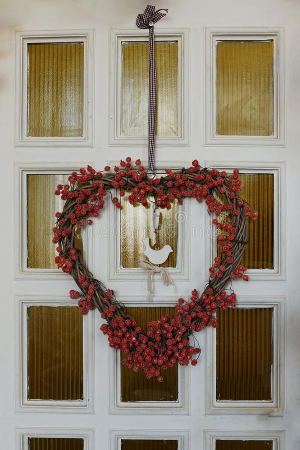 White wooden front door decorated in autumn, with red leaves, berries and a wreath. White wooden front door decorated in autumn, with red leaves berries and a stock photography