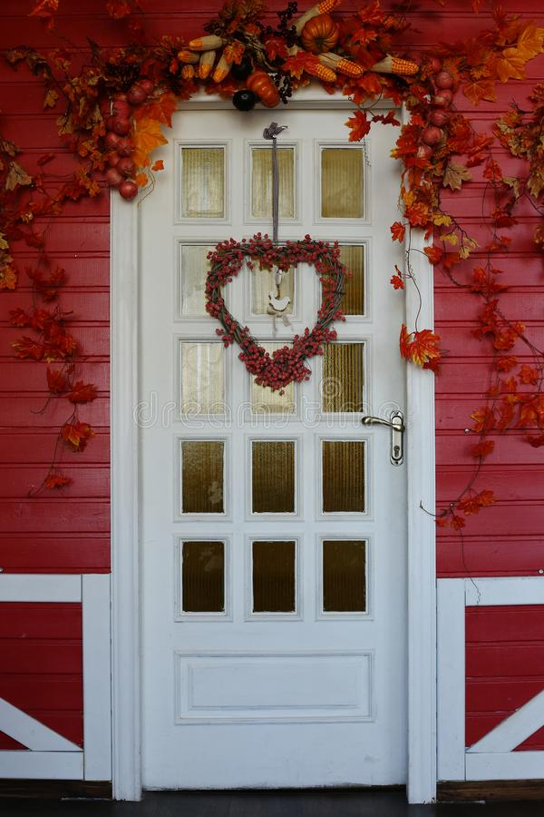 White wooden front door decorated in autumn, with red leaves, berries and a wreath. White wooden front door decorated in autumn, with red leaves berries and a stock photos