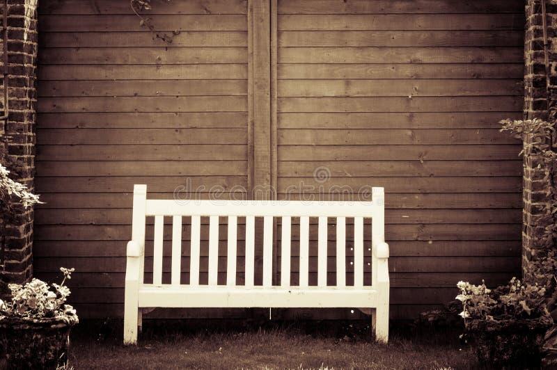White Wooden Garden Bench In English Garden Stock Image