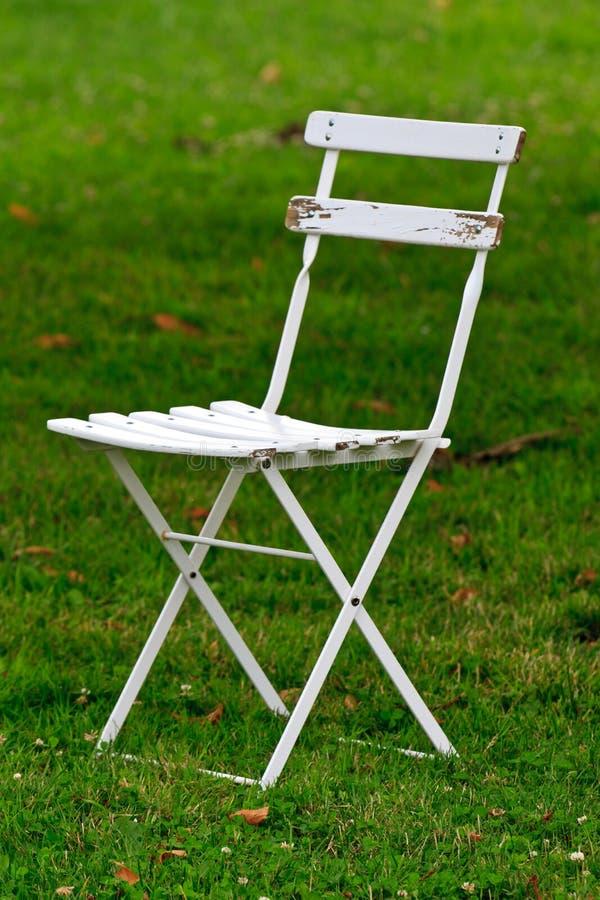 White wooden garden chair. (on green lawn stock photo