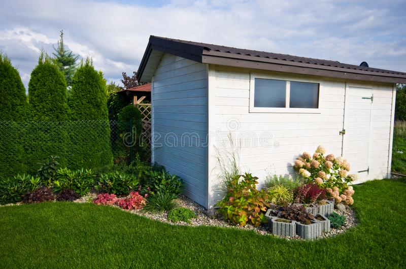 White wooden garden shed or hut with flowers and plants royalty free stock images
